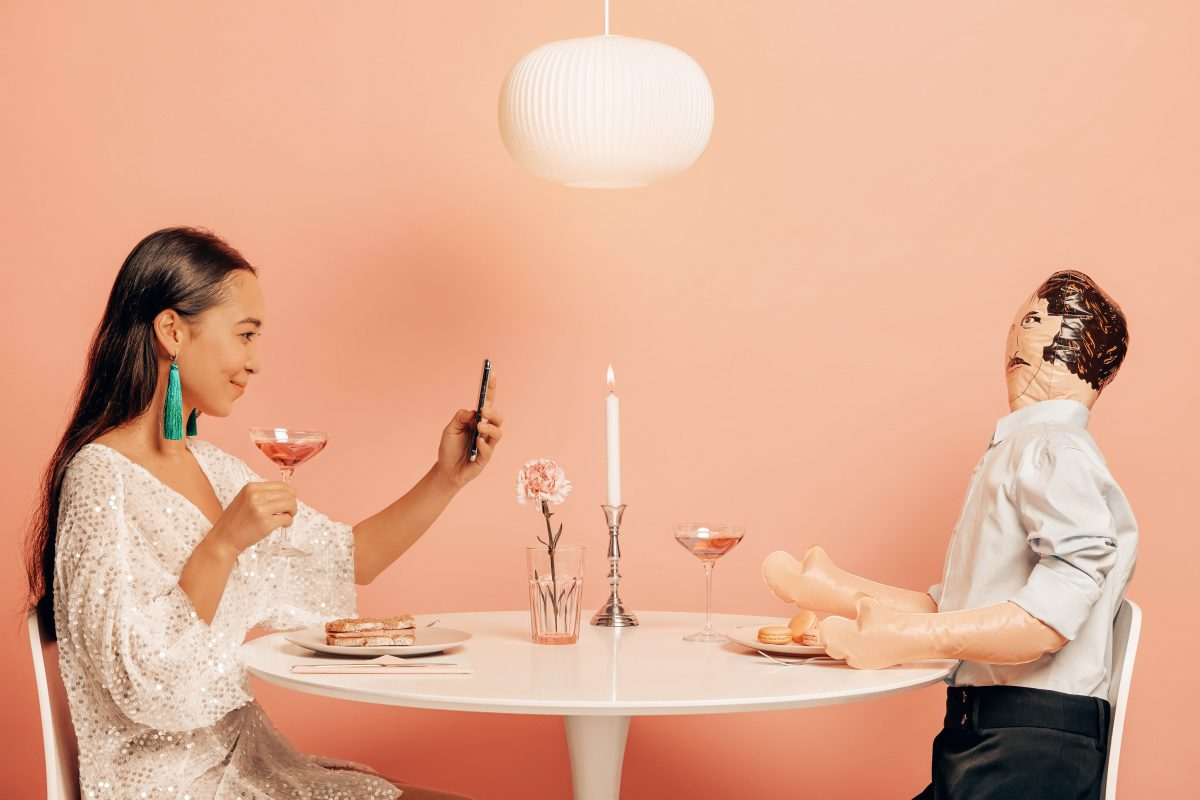 Lovely cheerful woman makes photo of herself on modern smartphone, drinks cocktail, takes picture to update profile in social networks simulates relationship has dinner with man doll not to feel bored